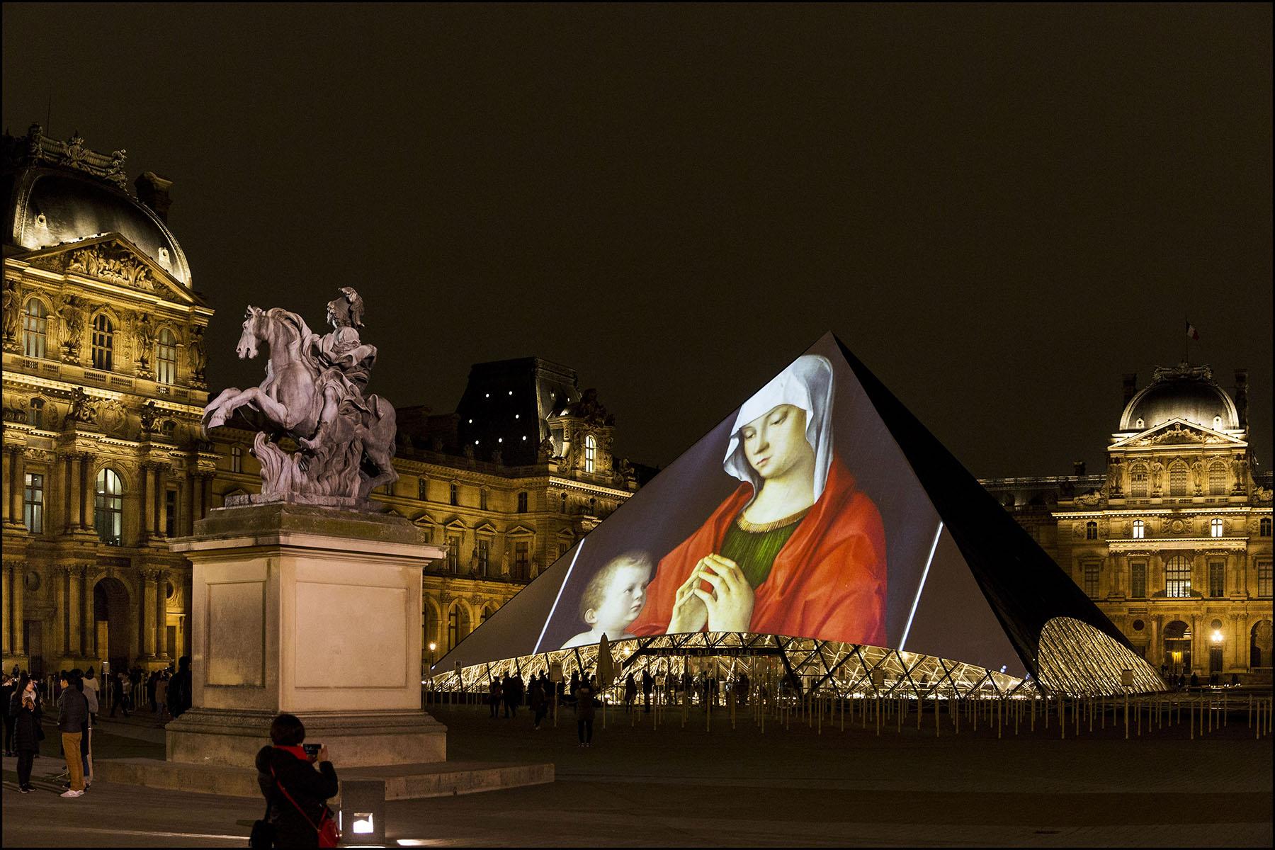 Projection d'images d'oeuvres du Louvre Abu Dhabi sur la pyramide du Louvre de Paris.
