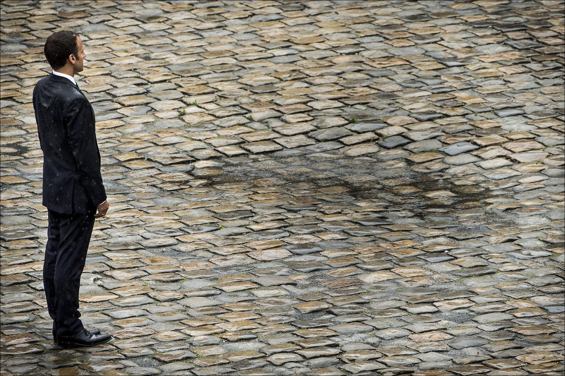 Emmanuel MACRON sous la pluie lors d'une cérémonie aux Invalides.
