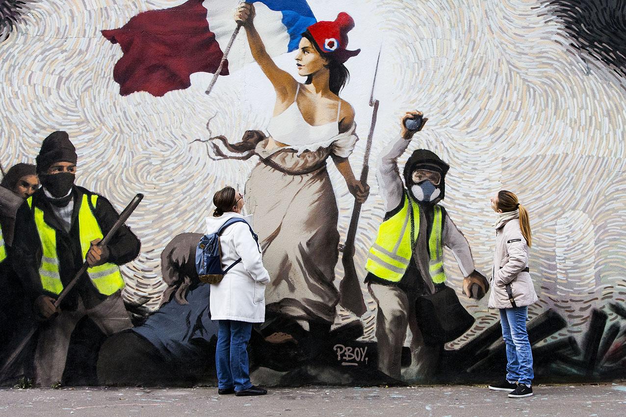 """Une fresque """"gilets jaunes"""" inspirée de Delacroix sur un mur de Paris.  Le street artiste Pascal BOYART (PBOY) a réalisé, en solidarité avec les """"gilets jaunes"""", une fresque sur un mur de Paris qui présente une version détournée de """"La Liberté guidant le peuple"""" d'Eugène Delacroix, célèbre tableau sur la Révolution de juillet 1830. Le spectateur doit résoudre une énigme en observant la fresque, trouver un """"puzzle bitcoin"""", une clé privée qui lui permettra de toucher 1.000 euros"""