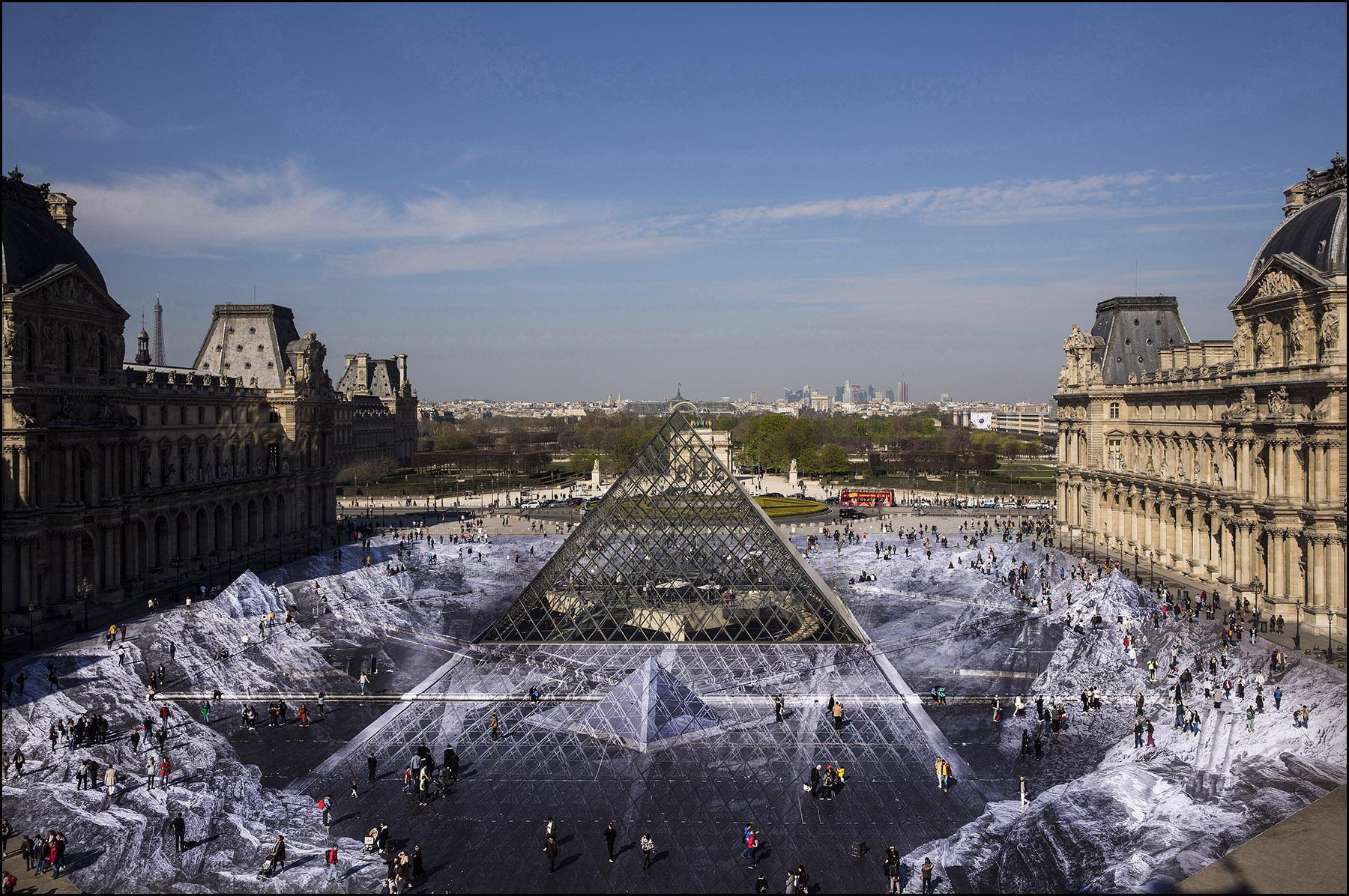 Dans la Cour Napoléon du Louvre, tout autour de la pyramide qui fête ses trente ans, l'artiste JR, a installé un immense collage en trompe-l'œil.  L'installation intitulée «  le secret de la grande pyramide », a été réalisée à partir d'un collage photographique créé par anamorphose.